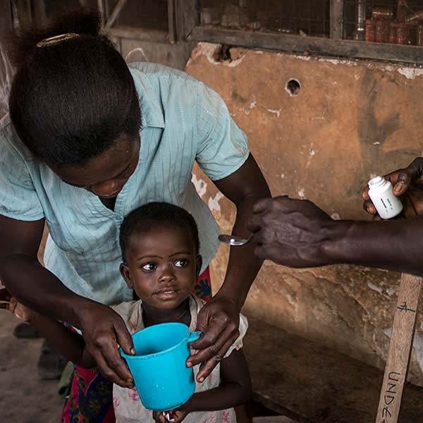 A child receives onchocerciasis medication from a volunteer distributor in Ghana