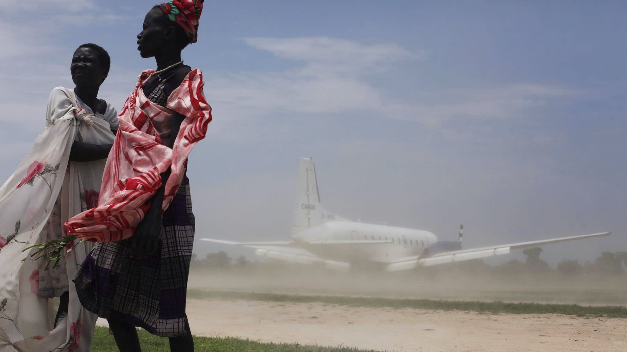 Women try to avoid dust as a plane, carrying nutrition supplements brought in by Medecins Sans Frontieres (MSF), lands in Leer July 15, 2014. The MSF hospital was giving service to over 200,000 people before it was looted and burned during fighting in late January and early February. The Hospital currently attends 1400 malnourished children according to Medecins Sans Frontieres. REUTERS/Andreea Campeanu (SOUTH SUDAN - Tags: HEALTH POLITICS SOCIETY FOOD TRANSPORT TPX IMAGES OF THE DAY) - RTR3YSC7