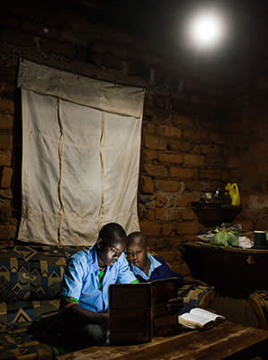 Erasmus Wambua, a schoolboy, left, studies at home using a book illuminated by a single electric LED lightbulb, powered by M-Kopa solar technology, in Ndela village, Machakos county, in Kenya, on Wednesday, July 22, 2015