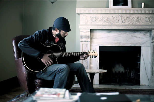 Cenac playing guitar in the film