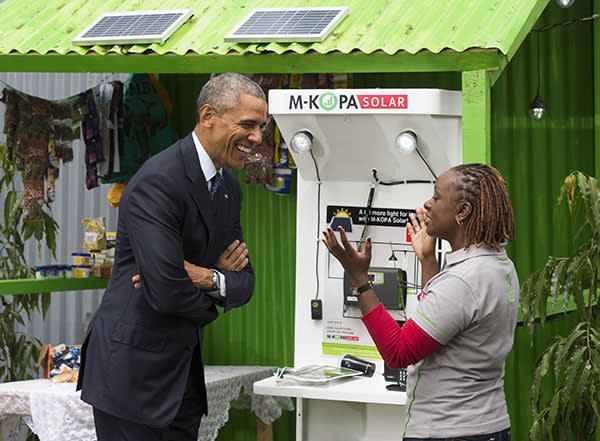 US President Barack Obama (L) talks with June Muli, head of Customer Care at M-Kopa, about solar power during the Power Africa Innovation Fair