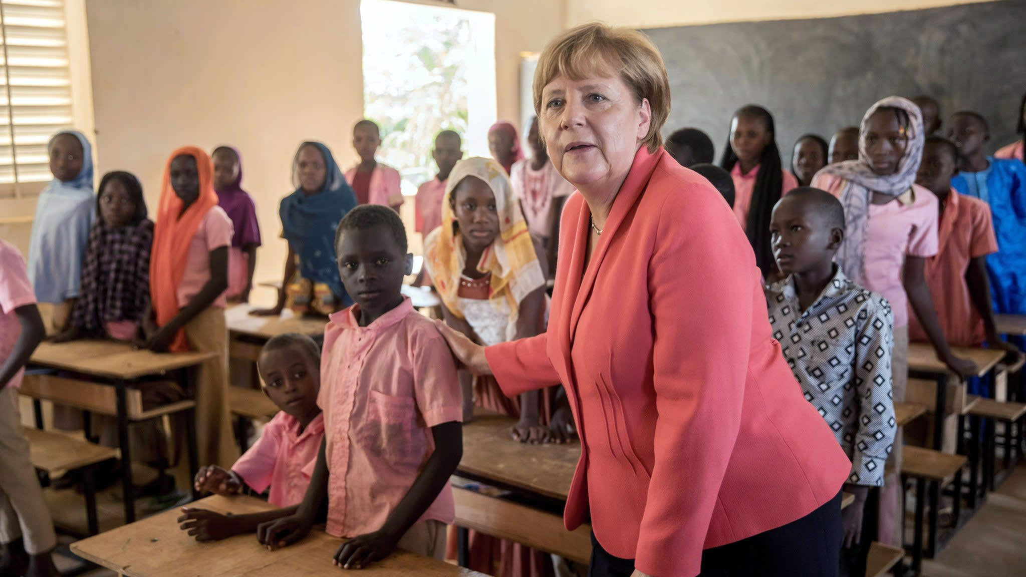 German Chancellor Angela Merkel (CDU) speaks with primary school students from the Goudell II. school in Niamey, Niger, 10 October 2016. Chancellor Merkel is on a three-day trip through Africa with stops in Mali, Niger and Ethiopia. Photo: MICHAEL KAPPELER/dpa
