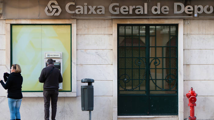 """A customer uses an automated teller machine (ATM) outside a Caixa Geral de Depositos SA bank branch in Lisbon, Portugal, on Saturday, Jan. 11, 2014. Portugal's Secretary of State for Treasury Isabel Castelo Branco said she """"estimates"""" it will be possible for the country to sell bonds through auctions before its bailout program ends in the middle of May. Photographer: Mario Proenca/Bloomberg"""