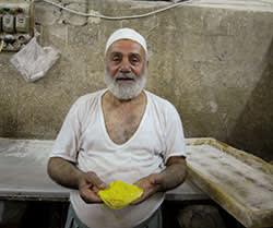 A baker in Souk el-Srijeh, Damascus with a ka'ket el-Eid or Eid cookie