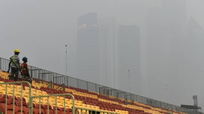 Workers install spectators seats for the Formula One street circuit as financial district buildings are shrouded with haze in Singapore on September 14, 2015. Helicopters water-bombed raging forest fires that have cloaked parts of Indonesia in thick haze and pushed air quality to unhealthy levels in neighbouring Singapore and Malaysia. AFP PHOTO / ROSLAN RAHMAN (Photo credit should read ROSLAN RAHMAN/AFP/Getty Images)