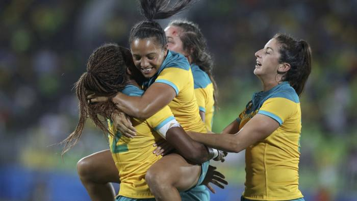 2016 Rio Olympics - Rugby - Women's Gold Medal Match Australia v New Zealand - Deodoro Stadium - Rio de Janeiro, Brazil - 08/08/2016. Ellia Green (AUS) of Australia, Amy Turner (AUS) of Australia and Chloe Dalton (AUS) of Australia celebrate their win over New Zealand. REUTERS/Phil Noble (BRAZIL - Tags: SPORT OLYMPICS SPORT RUGBY TPX IMAGES OF THE DAY) FOR EDITORIAL USE ONLY. NOT FOR SALE FOR MARKETING OR ADVERTISING CAMPAIGNS.