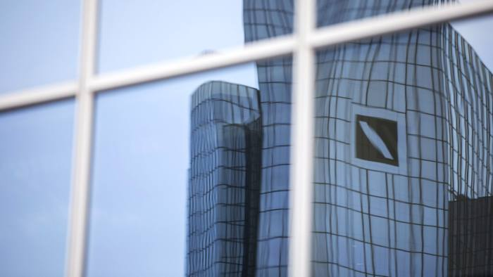 The twin tower skyscraper headquarter offices of Deutsche Bank AG are reflected in a neighboring building's windows in Frankfurt, Germany, on Monday, Jan. 2, 2017. Deutsche Bank is fighting 47 civil lawsuits from investors claiming losses from the manipulation of interbank lending rates, according to a regulatory filing. Photographer: Alex Kraus/Bloomberg
