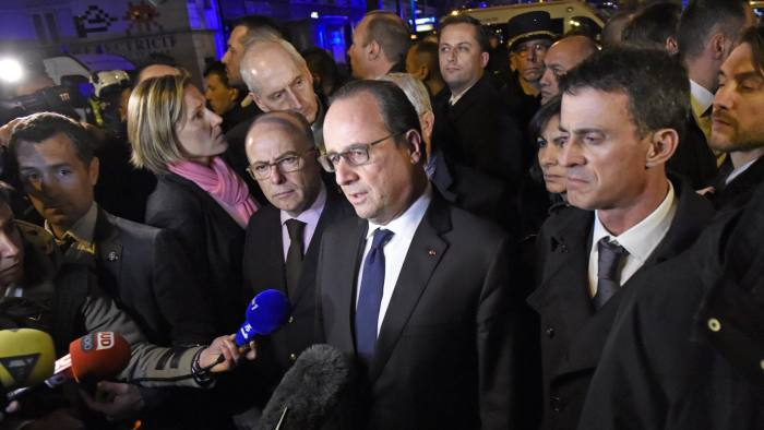 "French President Francois Hollande (C), flanked by French Interior Minister Bernard Cazeneuve (Rear L) and French Prime Minister manuel Valls (R) addresses reporters near the Bataclan concert hall in central Paris, early on November 14, 2015. A number of people were killed in an ""unprecedented"" series of bombings and shootings across Paris and at the Stade de France stadium on November 13, and the death toll looked likely to rise as sources said dozens had been killed at the Bataclan popular music venue. AFP PHOTO / MIGUEL MEDINA"