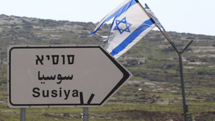 """An Israeli flag flies near a sign indicating the way to the Palestinian village of Susya, south-east of Hebron, in the Israeli-occupied West Bank, on February 10, 2016. Israel's High Court ruled in May 2015 that Susya's 340 residents could be relocated and its structures demolished, which Human Rights Watch derided as """"a grave breach"""" of Israel's obligations to the Palestinian populace under its military rule. / AFP / HAZEM BADER (Photo credit should read HAZEM BADER/AFP/Getty Images)"""