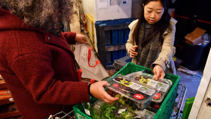 FoodCycle volunteers Clare Allen (L) and Renny Yeun (R) collect food donated by Waitrose supermarket in London on December 21, 2016. One of Europe's worst offenders on food waste, Britain is beginning to get its act together thanks to a surge in volunteer initiatives that help the poor as well as creating a bit of seasonal cheer. / AFP / BEN STANSALL / TO GO WITH AFP STORY by ROSIE SCAMMELL (Photo credit should read BEN STANSALL/AFP/Getty Images)