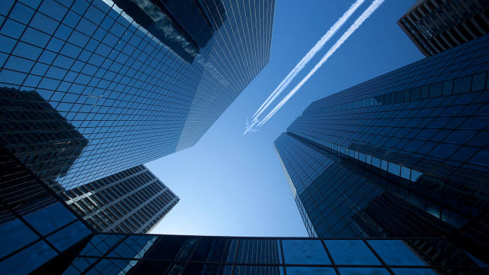 A large jet passes over modern skyscrapers leaving a sharp contrail.
