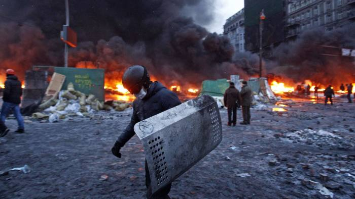 A pro-European protester carries a shield during street violence in Kiev January 23, 2014. Ukrainian opposition leaders emerged from crisis talks with President Viktor Yanukovich on Wednesday saying he had failed to give concrete answers to their demands, and told their supporters on the streets to prepare for a police offensive