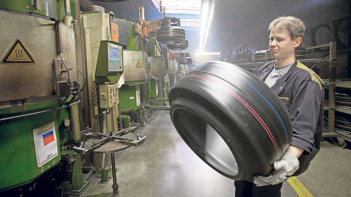 An employee carries a tire at the Continental AG factory in Aachen, Germany, on Wednesday, Jan. 6, 2010