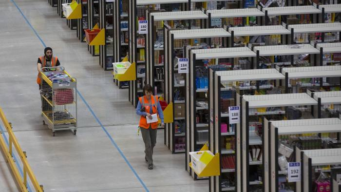 An employee pushes a cart as he processes customer orders ahead of shipping at one of Amazon.com Inc.'s fulfillment centers in Rugeley, U.K., on Monday, Dec. 2, 2013. Online retailers in the U.K. are anticipating their busiest day as shoppers flush with end-of-month pay-checks seek Christmas deals on the Web. Photographer: Simon Dawson/Bloomberg