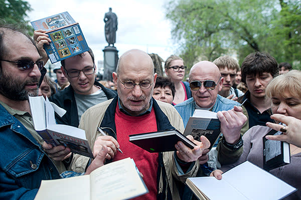 "Grigory Chkhartishvili, a detective novelist who is known under the pen name Boris Akunin, signs books during a protest ""stroll"" he helped organize in Moscow on May 13, 2012"
