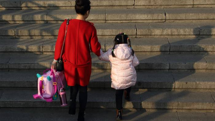 A girl walks up a flight of stairs with her mother in Beijing, China, on Saturday, Nov. 8, 2014. Chinese President Xi Jinping relaxed China's family-planning policy last year by allowing couples to have two children if either parent is an only child. Photographer: Tomohiro Ohsumi/Bloomberg