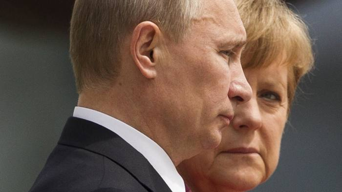 German Chancellor Angela Merkel and Russian President Vladimir Putin (L) listen to their national anthems before talks at the Chancellery in Berlin, June 1, 2012. REUTERS/Thomas Peter (GERMANY - Tags: POLITICS CIVIL UNREST TPX IMAGES OF THE DAY) - RTR32XLW
