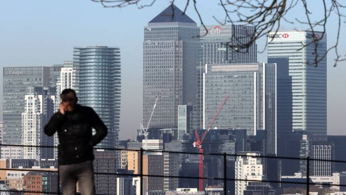 A man speaks on a mobile phone against a backdrop of the offices of global financial institutions, including Citigroup Inc., State Street Corp., Barclays Plc HSBC Holdings Plc, and the commercial office block No. 1 Canada Square, in Canary Wharf in London, U.K., on Tuesday, Nov 29, 2016. The Bank of England added a new, higher bar to its third round of public stress tests. Photographer: Chris Ratcliffe/Bloomberg