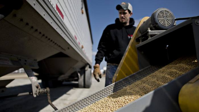 Crop consultant Kyle Anderson monitors Monsanto Co. Asgrow soybeans traveling along a conveyor during a delivery at the Crop Protection Services (CPS) facility in Manlius, Illinois, U.S., on Friday, March 20, 2015. Monsanto Co. is scheduled to release earnings on April 1. Photographer: Daniel Acker/Bloomberg *** Local Caption *** Kyle Anderson