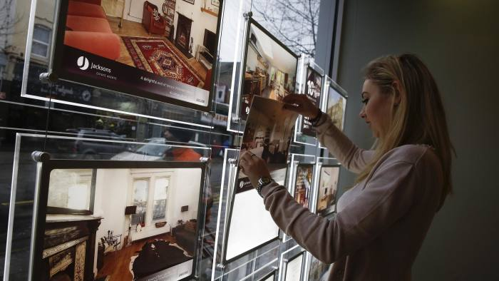 An estate agent arranges a photographic display of exteriors and interiors of available residential properties in London, U.K., on Monday, Dec. 30, 2013. U.K. house prices rose in December and will extend gains in 2014, led by London and southeast England, Hometrack Ltd. said. Photographer: Simon Dawson/Bloomberg