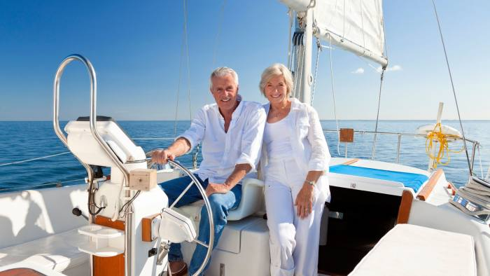 DE3TRN A happy senior couple sitting at the wheel of a sail boat on a calm blue sea