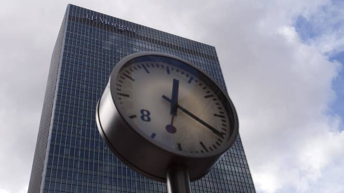 A clock stands in front of the offices of JPMorgan Chase & Co. in the business and financial district of Canary Wharf in London, U.K., on Tuesday, April 10, 2012. Bruno Iksil, a London-based trader in JPMorgan Chase & Co.'s chief investment office, has built derivatives positions linked to corporate credit that are so big he's moved markets, according to hedge fund managers and dealers. Photographer: Simon Dawson/Bloomberg