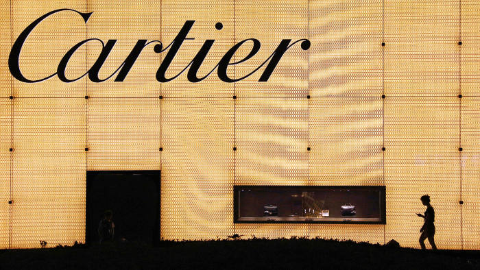 A pedestrian on their phone walks past a Cartier store in Shanghai