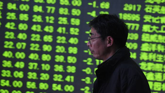 An investor walks past a screen showing stock prices at a securities company in Hangzhou, in China's eastern Zhejiang province on February 25, 2016. Shanghai stocks closed down more than six percent on February 25, slammed by worries over China's slowing economy and tight liquidity, dealers said. CHINA OUT AFP PHOTO / AFP / AFP