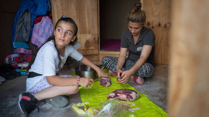 An Iraqi-Kurdish family prepares dinner in the Grande-Synthe camp