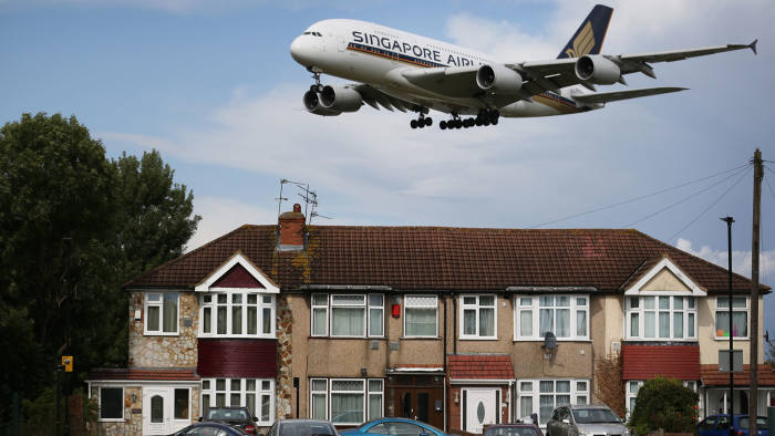 A passenger plane comes into land near housing at Heathrow Airport on August 11, 2014 in London, England