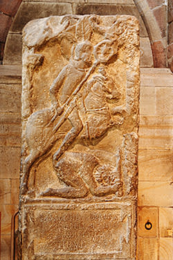A tombstone at Hexham Abbey depicting a Roman soldier riding over a barbarian enemy