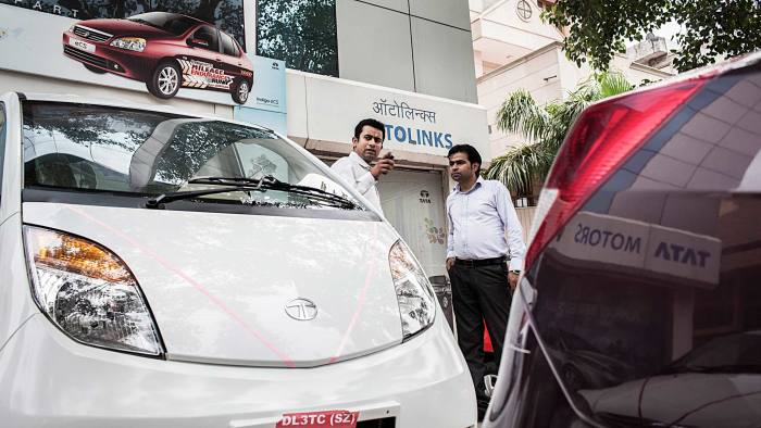A customer negotiates with a sales person at a Tata Motors Ltd. dealership in New Delhi, India, on Thursday, July 26, 2012.