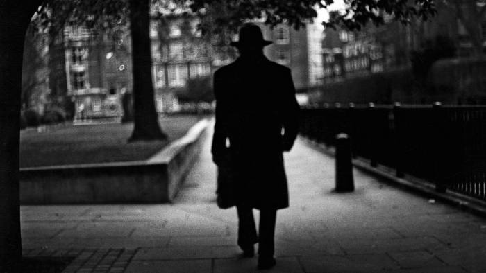 A black and white image of a man walking in a park