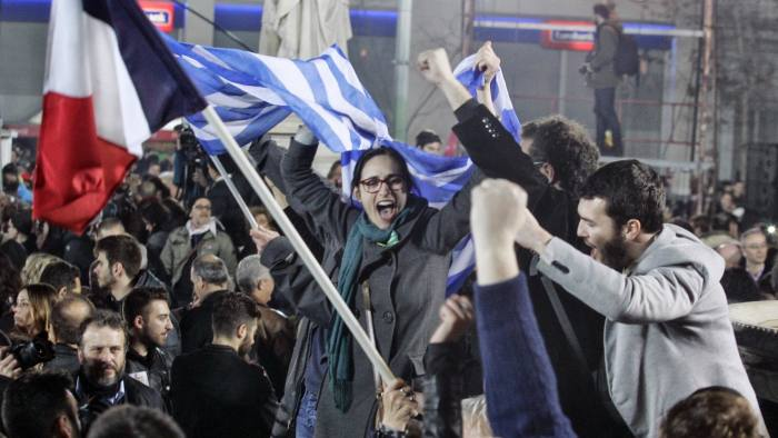 ATHENS, GREECE - JANUARY 25: A supporter of Alexis Tsipras, leader of Syriza left-wing party, holds the Greek and French  flag during a rally outside Athens University Headquarters January 25, 2015 in Athens, Greece. According to the latest opinion polls, the left-wing Syriza party are poised to defeat Prime Minister Antonis Samaras' conservative New Democracy party in the election, which has taken place today. European leaders fear that Greece could abandon the Euro, write off some of its national debt and put an end to the country's austerity by renegotiating the terms of its bailout if the radical Syriza party comes to power. Greece's potential withdrawal from the eurozone has become known as the 'Grexit'. (Photo by Milos Bicanski/Getty Images)