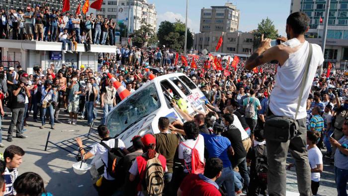 Protesters prepare to roll a police car over in Taksim Square.