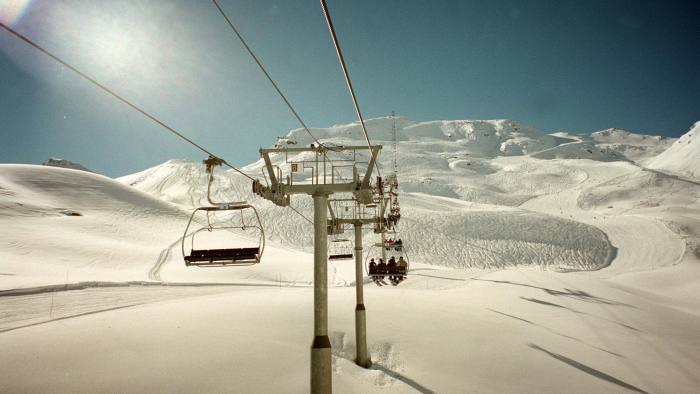 at the Three Valleys skiing resort in the French Alps, France. Skiers and snowboarders take the ski lift over a run on Vallee de Meribel at the Three Valleys skiing resort in the French Alps, France.
