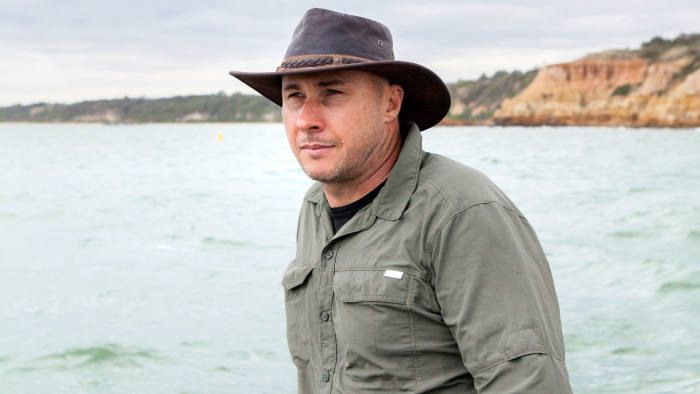 Jeffrey Condon, former manager of the Nomad Lodges in Tanzania, inspects a rough ocean at the Port Philip Bay foreshore, Melbourne, Australia. While stationed in Tanzania, Condon taught a young pelican how to fish and even fly after it had been displaced from it's family. In teaching the bird basic survival skills, Condon hopes that one day it might be able to rejoin it's flock. // Katrin Koenning for Financial Times Magazine, 27/11/2015, Melbourbe, Victoria, Australia.