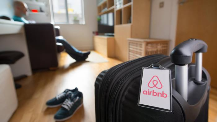 GD5G54 A man sits alone near to a suitcase with an Airbnb branded luggage tag in an otherwise empty apartment (Editorial use only).
