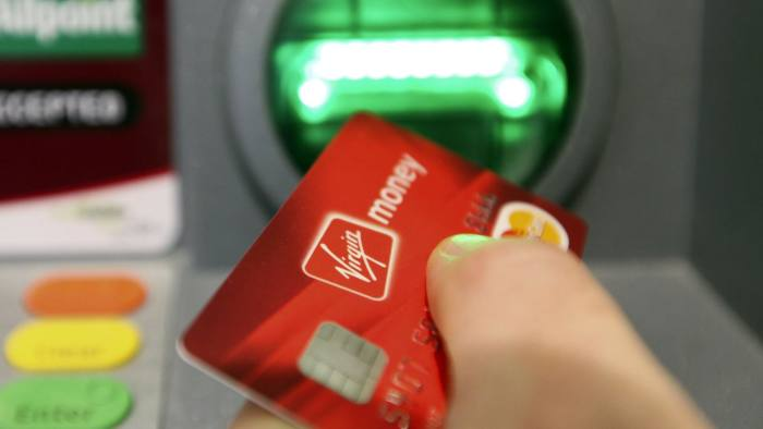 A customer uses an automated teller machine (ATM) inside the Virgin Money Holdings U.K. Ltd.'s 'Money Lounge', in this arranged photograph, in Norwich, U.K., on Monday, Feb. 13, 2012. Bank of England officials pumped another 50 billion pounds ($79 billion) into the U.K. economy to protect a nascent recovery from the threat posed by Europe's debt crisis. Photographer: Chris Ratcliffe/Bloomberg