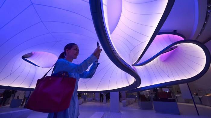 A woman uses a mobile phone to photograph a new gallery, Mathematics: The Winton Gallery, inside the Science Museum during a press view in London on December 7, 2016. The Gallery was designed by Zaha Hadid Architects. / AFP / NIKLAS HALLE'N (Photo credit should read NIKLAS HALLE'N/AFP/Getty Images)