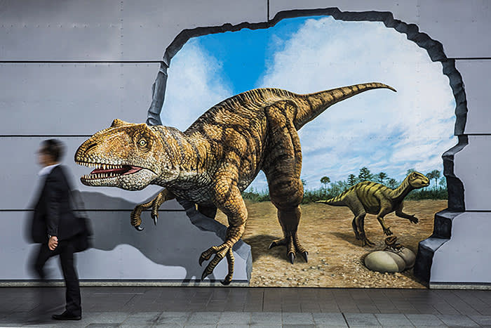 Bloomberg Best of the Year 2017: A pedestrian walks past a mural showing dinosaurs on a wall outside the Fukui station in Fukui, Japan, on Wednesday, Oct. 11, 2017. Photographer: Shiho Fukada/Bloomberg