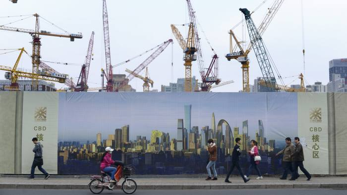 Pedestrian walk past a construction site in Beijing on April 1, 2015. China's manufacturing activity expanded in March for the first time since December, the government said on April 1, a bright spot as the world's second-largest economy fights a broad slowdown in growth. AFP PHOTO /WANG ZHAO (Photo credit should read WANG ZHAO/AFP/Getty Images)