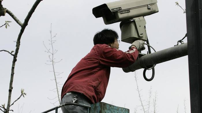 man repairs a security video camera for police surveillance overlooking the street in front of the Japanese embassy in Beijing, 10 April 2005. China appealed for calm a day after an anti-Japanese demonstration which drew up to 10,000 protesters turned violent when bottles and rocks were hurled at the Japanese embassy. China's foreign ministry said a huge police force had been mobilized to keep order after Saturday's protests, the biggest demonstration in Beijing in six years. AFP PHOTO/Frederic J. BROWN (Photo credit should read FREDERIC J. BROWN/AFP/Getty Images)