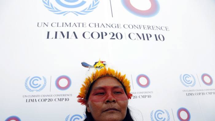 An Indian woman from Ecuador poses for a photo at the Climate Change Conference in Lima, Peru, Tuesday, Dec. 9, 2014. Delegates from more than 190 countries are meeting in Lima, to work on drafts for a global climate deal that is supposed to be adopted next year in Paris. (AP Photo/Juan Karita)