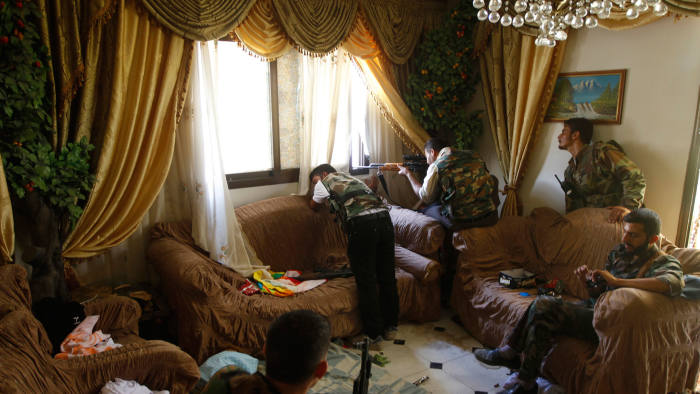 A Free Syrian Army fighter fires his rifle from a house in the city of Aleppo