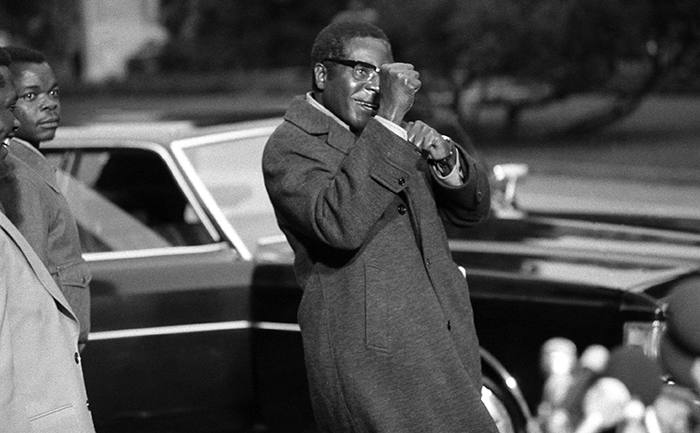 Robert Mugabe, an African leader taking part in the Rhodesia conference in Geneva, jokingly puts up his fists as he encounters newsmen, Nov. 4, 1974. (AP Photo)