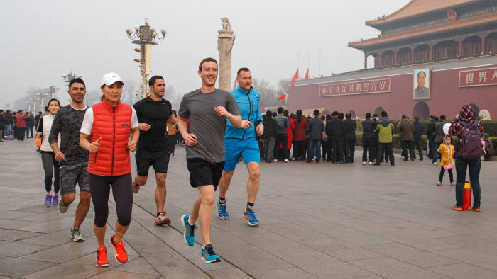 This handout picture taken and provided by Facebook on March 18, 2016, shows Facebook CEO Mark Zuckerberg (front R, grey shirt) running past Tiananmen Gate, the entrance to the Forbidden City, in Beijing