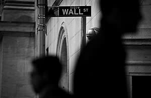 Pedestrians walk past a Wall Street sign and security camera in front of the New York Stock Exchange (NYSE) in New York, U.S., on Wednesday, April 24, 2013