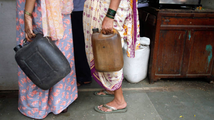 Women hold empty kerosene containers while queuing at a local ration shop, Mumbai, India