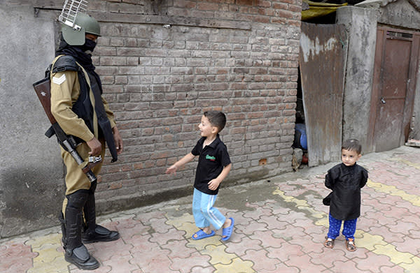 Indian paramilitary trooper stands guard as Kashmiri children look on during a curfew and strike called following the killing of a Kashmiri student in downtown Srinagar on June 9, 2017. The death of a student killed by troops in Kashmir sparked new anti-India demonstrations on June 7. Hundreds of students and villagers joined a rally in the town of Shopian, south of the Indian-administered Kashmir capital of Srinigar, during the funeral of Adil Farooq Magray. / AFP PHOTO / TAUSEEF MUSTAFATAUSEEF MUSTAFA/AFP/Getty Images